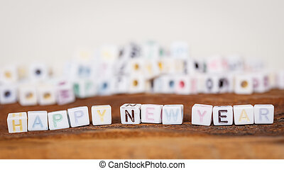 Happy new year written in letter beads on wood background
