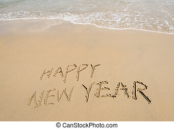 happy new year written in the sand