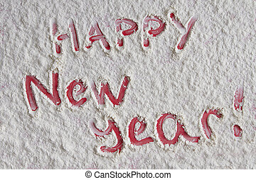 Happy new year written on white flour background