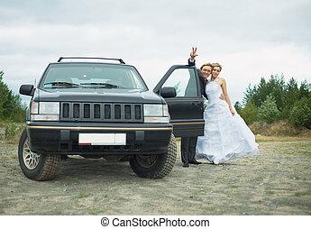 Happy newly-married couple says goodbye near car