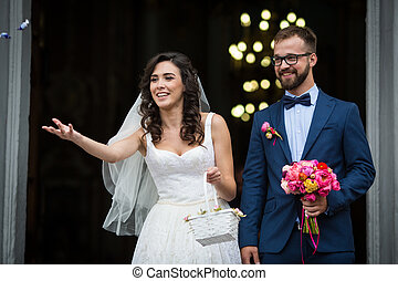Happy newlywed couple coming out of church, holding bouquet and throwing candy