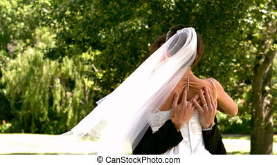 Happy newlywed couple in the park - Happy newlywed couple in...