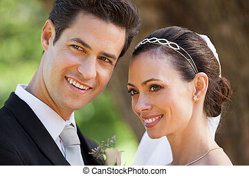 Happy newlywed couple looking away at park
