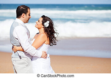 happy newlywed couple on beach