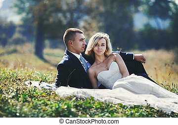 Happy newlywed couple relaxing & posing in a field at sunset