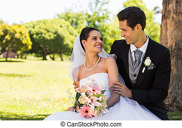 Happy newlywed couple sitting in park - Happy young newlywed...