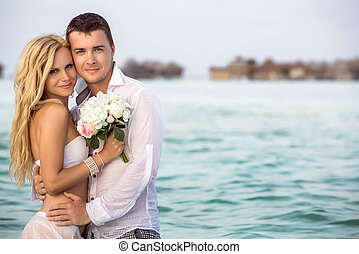 newlywed couple - Happy newlywed couple standing in water....