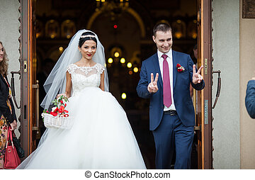 Happy newlywed romantic couple coming out of church after wedding ceremony with a candy basket