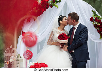 Happy newlywed romantic couple kissing at wedding aisle with red decorations and flowers