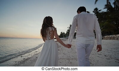 Happy newlyweds at sunset near the ocean. They walk barefoot along the sandy shore, holding hands, and look at each other with love. There are palm trees around them. A faraway Philippine boat. Shooting in motion.