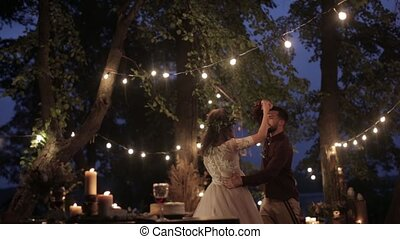 Happy newlyweds dance kiss - Young couple night lights...