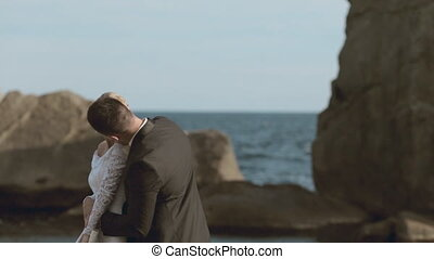 Happy newlyweds dancing on the seaside near cliffs