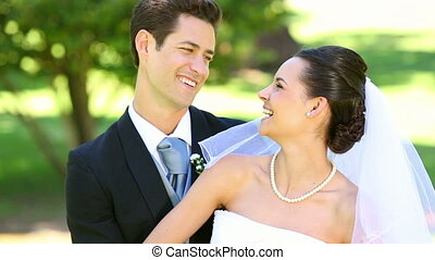 Happy newlyweds embracing each other in the park on a sunny...