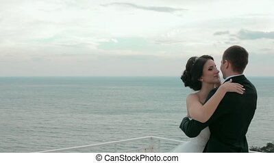 Happy newlyweds embracing near the sea