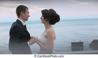 Happy newlyweds hugging and kissing while standing near the sea at sunset
