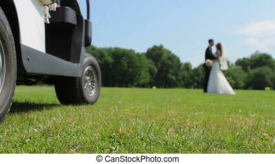 Happy newlyweds kissing on a golf course.