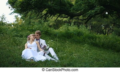 Happy newlyweds on nature - Happy newlyweds kissing on...