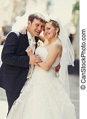 Happy newlyweds pose somewhere on the street