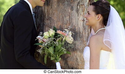 Happy newlyweds posing in the park beside a tree on a sunny...
