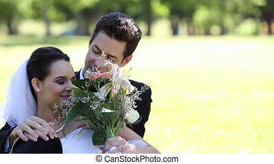 Happy newlyweds sitting in the park
