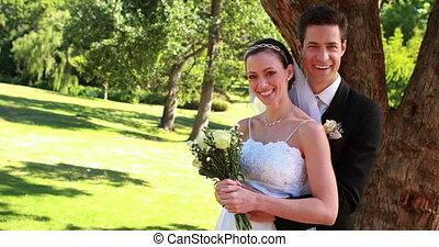 Happy newlyweds smiling at camera a - Happy newlyweds...