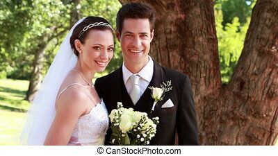 Happy newlyweds smiling at camera on a sunny day