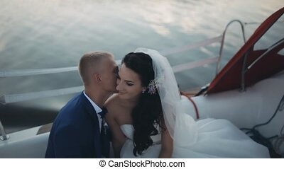 Happy newlyweds spending time on a sailboat in the open water together. Groom tenderly whispers in bride ear.