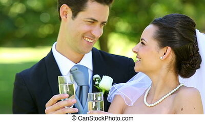 Happy newlyweds toasting with champagne