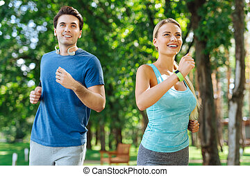 Happy nice active people enjoying running together