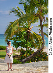 happy nice bride walk near beach on green grass under palms. Young woman in white dress on a beach