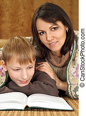 Happy nice Caucasian mom with her son reading a book