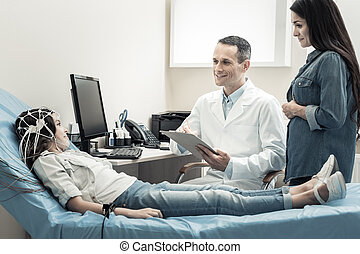 Happy nice doctor looking at his patient