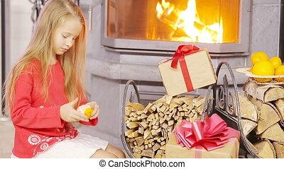 Happy nice girl opening christmas present near fireplace -...