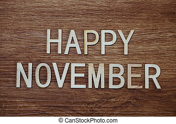 Happy November text message on wooden background