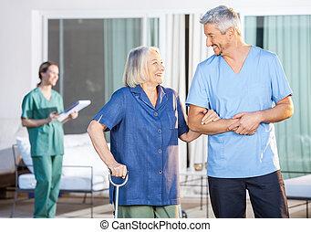 Happy Nurse Assisting Senior Woman To Walk