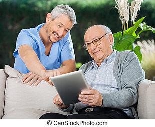 Happy Nurse Helping Senior Man In Using Tablet Computer -...