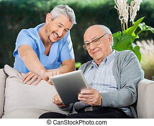 Happy Nurse Helping Senior Man In Using Tablet Computer -...