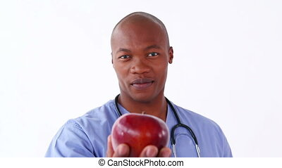 Happy nurse holding a red apple