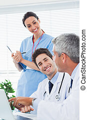 Happy nurse listening to doctors talking about something on their laptop in medical office