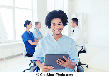 happy nurse with tablet pc over team at hospital