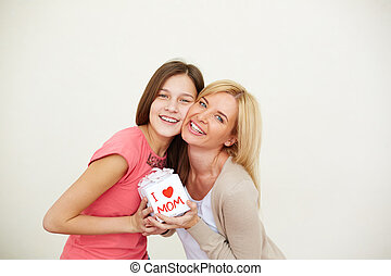 Happy occasion - Teenage girl and her mom with small present...
