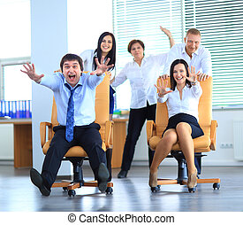 Happy office employees having fun at work in an office chair...