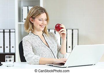 Happy office worker working holding an apple