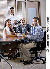Happy office workers meeting at table in boardroom working...