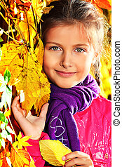 Portrait of a cute little girl posing at the autumn park.