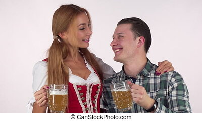 Happy Oktoberfest couple clinking beer mugs, smiling at each other