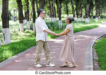 Happy old couple dancing in the park