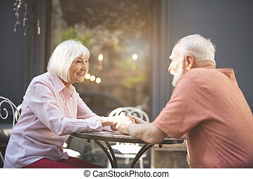 Happy old couple having dinner outdoors