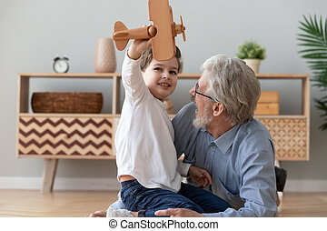 Happy old grandfather and cute grandson playing with wooden plane