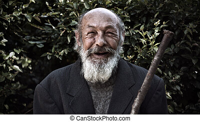happy old homeless - portrait of an elderly bearded man with...
